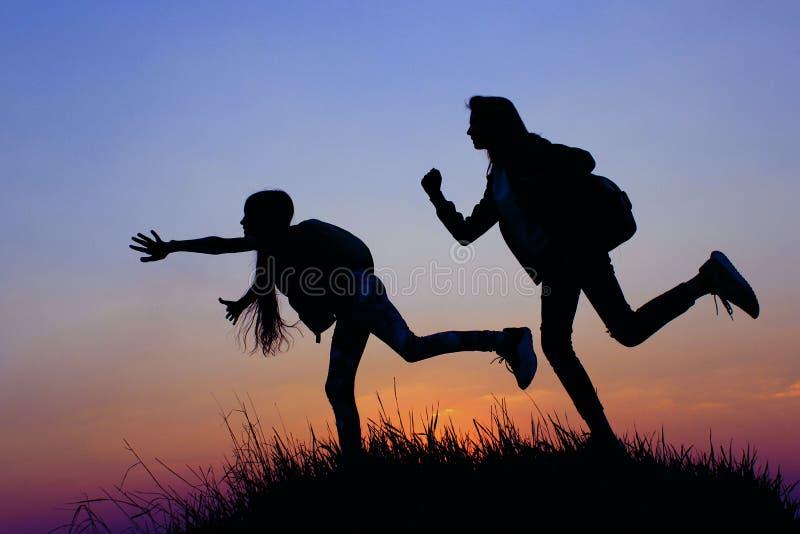 Kontur av a-unga flickor på en bergöverkant Unga flickor med ryggsäcken som tycker om solnedgång Kvinnliga vänner som utomhus spe arkivfoton