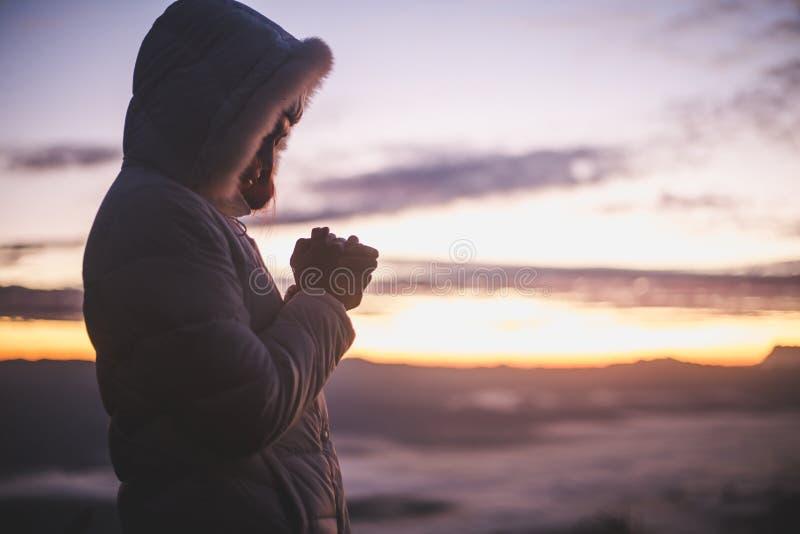 Kontur av unga mänskliga händer som ber till guden på soluppgång, Christian Religion begreppsbakgrund arkivfoto