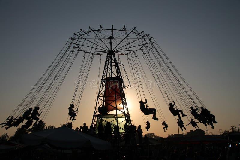 Kontur av ungdomarpå pariserhjulen och svängakarusellen i stopprörelse på solnedgångbakgrund royaltyfria bilder