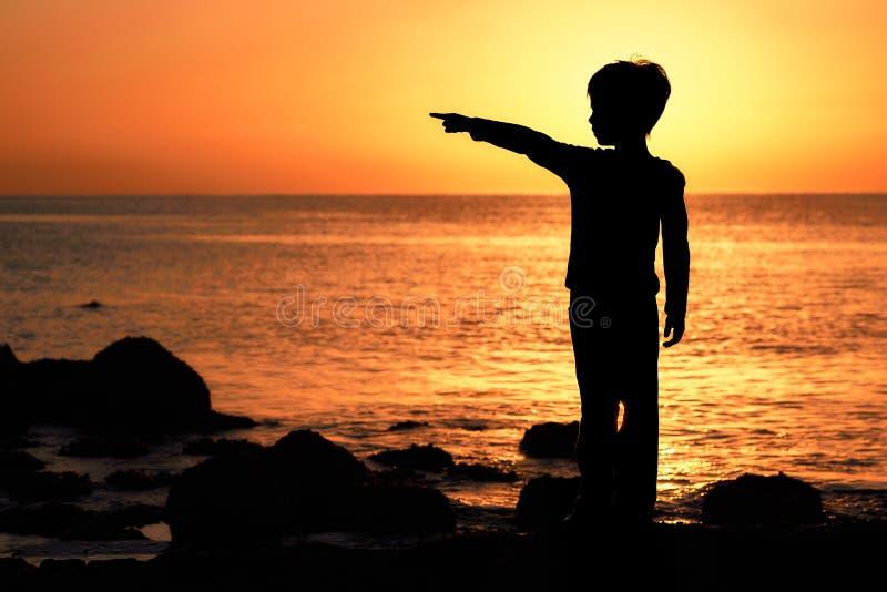 Kontur eines Jungen mit den Daumen angehoben bei Sonnenaufgangsonnenuntergang auf der Küste stockbild