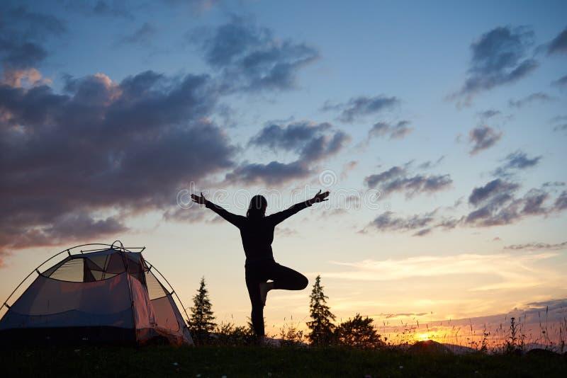 Kontur för bakre sikt av berget för yoga för sport det kvinnliga praktiserande överst på soluppgång royaltyfri foto