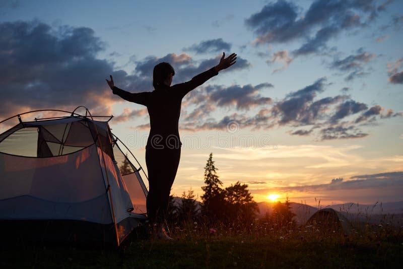 Kontur för bakre sikt av det kvinnliga anseendet med near campa för öppna armar i berg på soluppgång royaltyfria bilder
