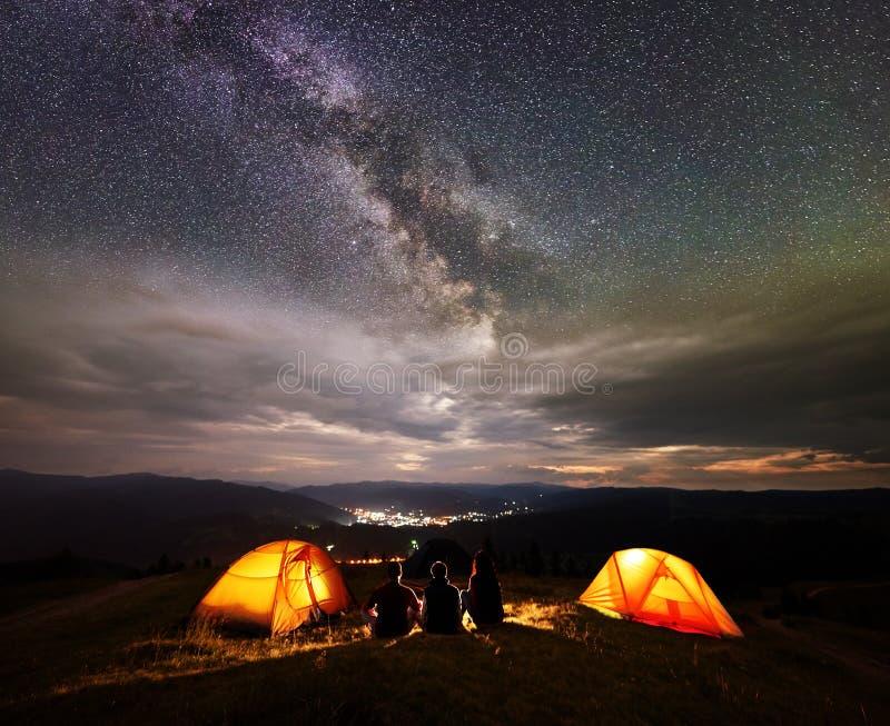 Kontur för bakre sikt av fyra personer som sitter bredvid läger i natt under himmel med många stjärnor arkivfoto