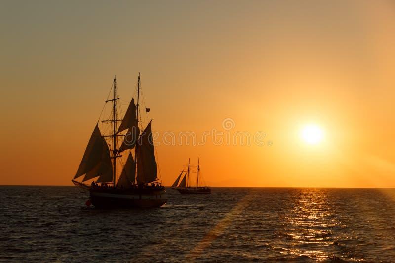 Kontur för seglingskepp i solnedgång på havet arkivbilder