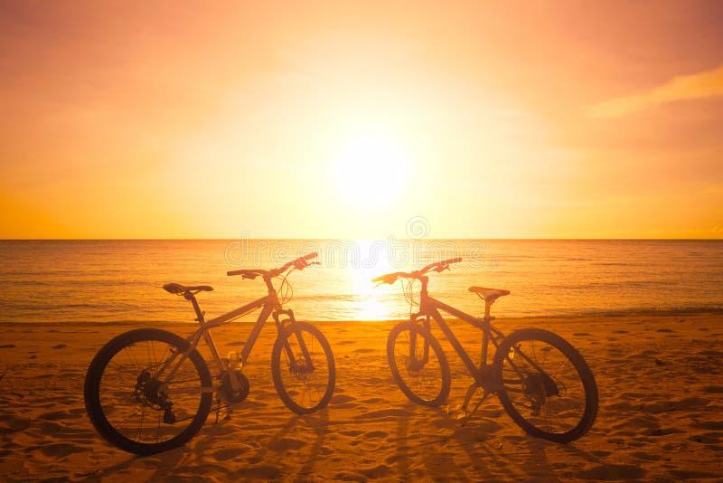 Kontur för två cykel på solnedgången nära havet fotografering för bildbyråer