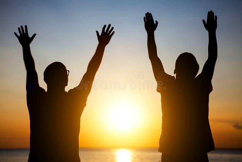 Kontur för två män på solnedgången arkivbild