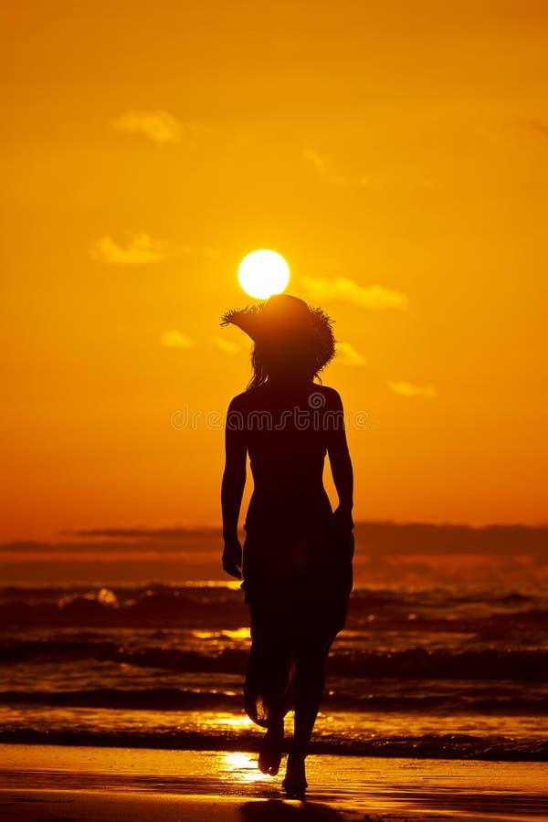 Kontur för ung kvinna på stranden i sommarsolnedgång royaltyfria bilder
