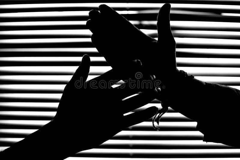 Kontur i monokrom av handskakningen av två män i fönstret som stänger med fönsterluckor med randigt ljus och skugga arkivfoton