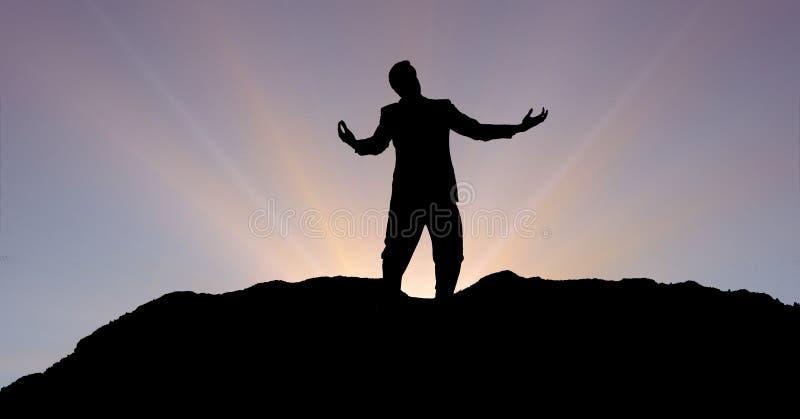 Konturaffärsman med armar som är utsträckta på berget under solnedgång royaltyfria foton