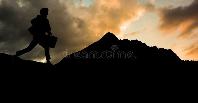 Konturaffärsmanspring på berget mot himmel arkivfoton