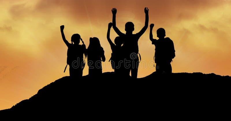 Konturbarn med armar lyftte på kullen mot himmel under solnedgång arkivbild