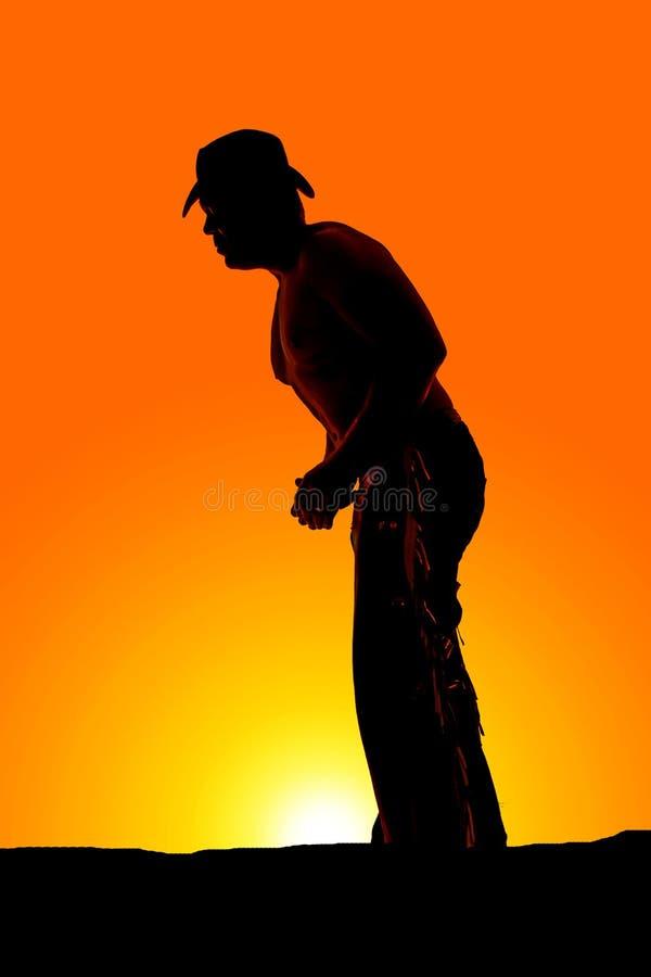 Konturcowboy som ingen skjortahatt lutar på framåtriktat royaltyfri foto
