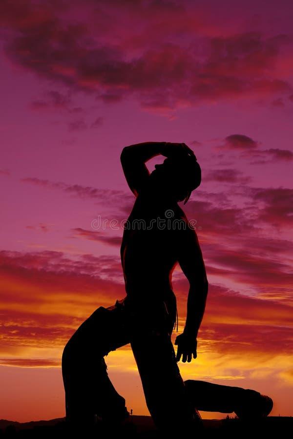 Konturcowboyen ingen skjorta knäfaller en knähand på hatten ser upp arkivbild