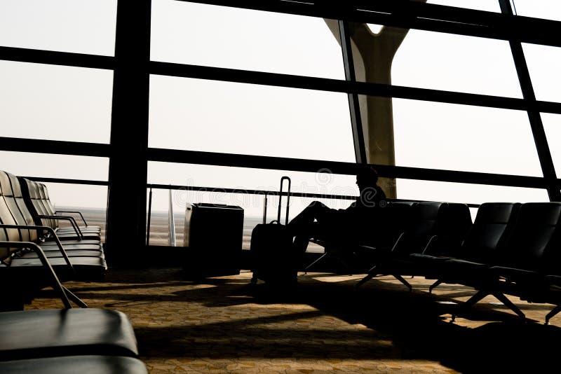 Konturer av affärsmannen på flygplatsen; vänta på de plana logiportarna royaltyfri bild