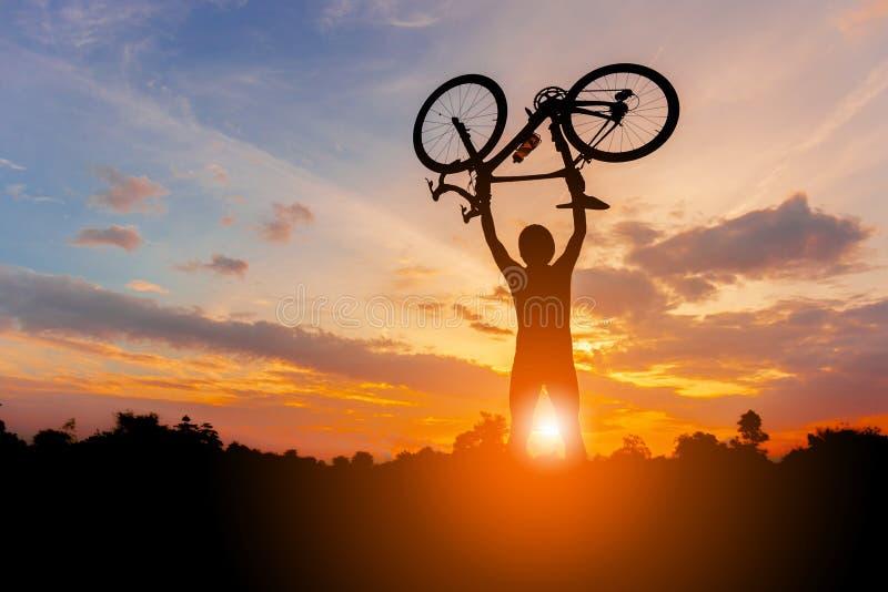 Konturer av cyklistmanhåll cyklar högt upp i solnedgånghimlen, arkivfoto