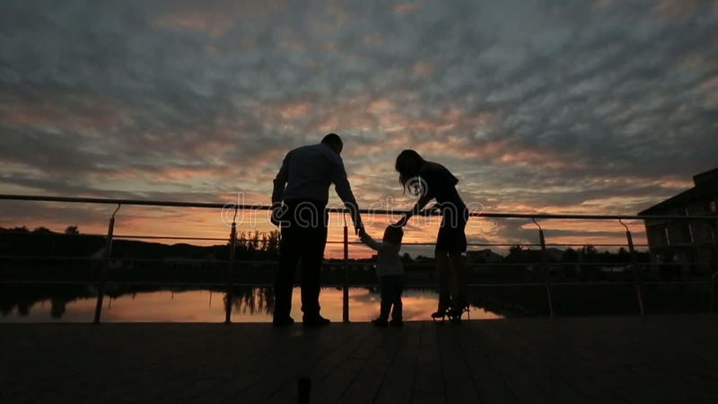 Konturer av den lyckliga familjen som tillsammans går på solnedgången