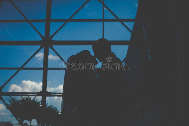 Konturer av den ursnygga lyckliga blonda bruden och den eleganta brudgumkramen arkivbilder