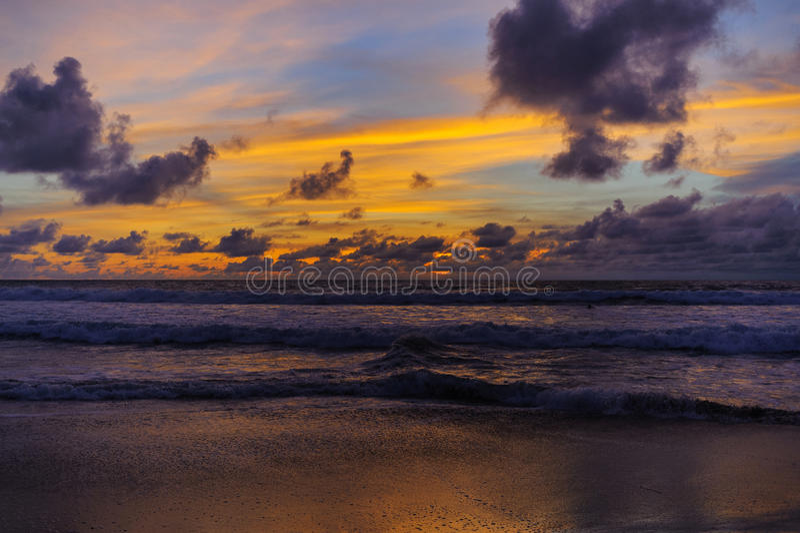 Konturer av en våg och moln på en färghimmel under solnedgång tropisk strandafton arkivfoto