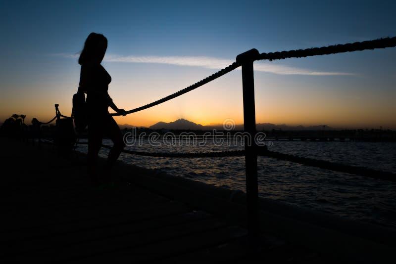 Konturer av ett flickaanseende på en pir nära havet mot bakgrunden av en solnedgång i bergen arkivfoton