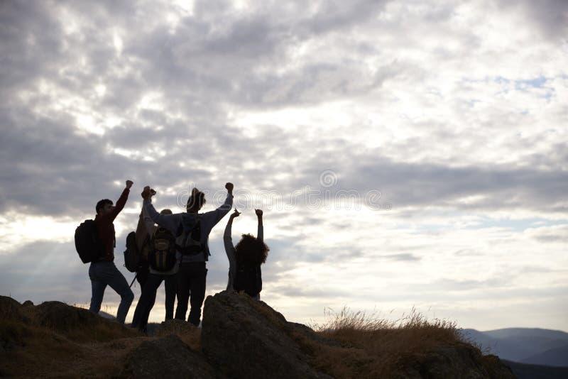 Konturer av fem unga vuxna vänner som firar på toppmötet efter en bergvandring, tillbaka sikt royaltyfri foto