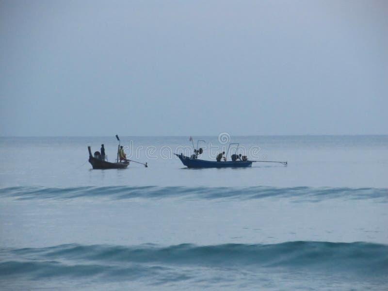 Konturer av fiskare med deras lång-tailed fartyg på havet på solnedgången royaltyfri foto