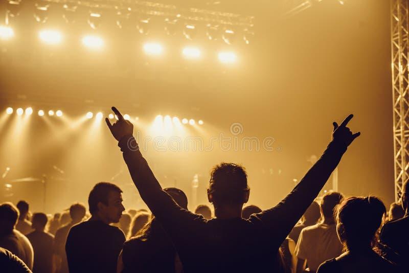 Konturer av folk i ett ljust i popet vaggar konsert framme av etappen Händer med gesthorn Det vaggar Parti i a royaltyfri fotografi