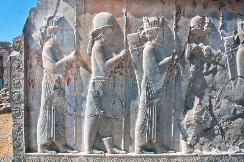 Konturer av folk i forntida dräkter på den förstörda stenbasreliefen fotografering för bildbyråer