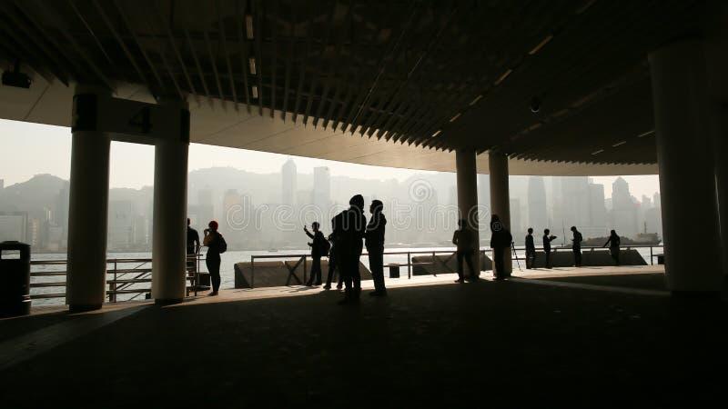 Konturer av folk i hamnen av Victoria i Hong Kong Sikt av havet och staden från inre bron arkivbilder