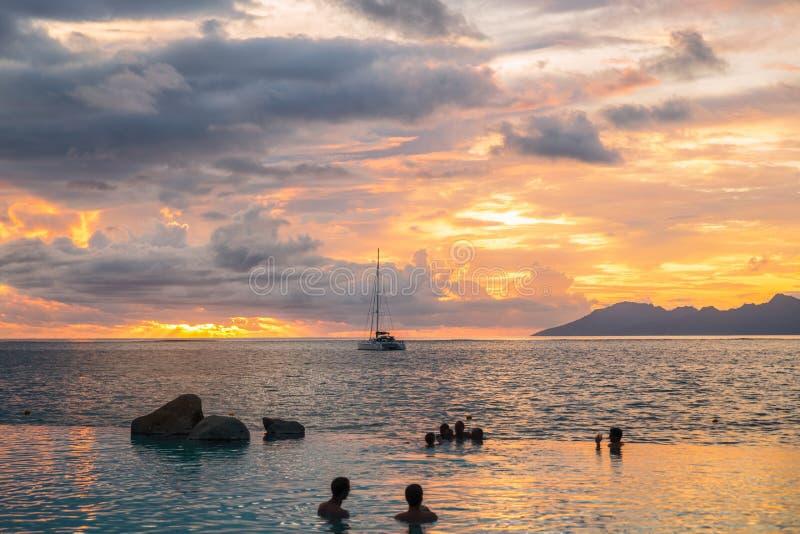 Konturer av folk i simbassängen som firar klyftasolnedgång arkivbilder