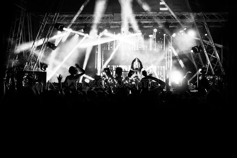Konturer av folk på en konsert framme av platsen i ljust ljus svart white royaltyfri fotografi