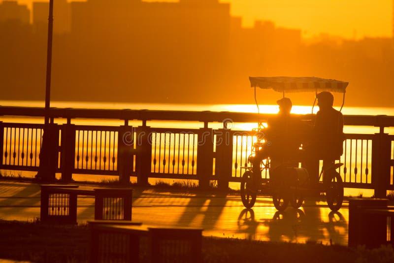 Konturer av folk på promenadridningen på mång--Seat cyklar på solnedgången arkivbild