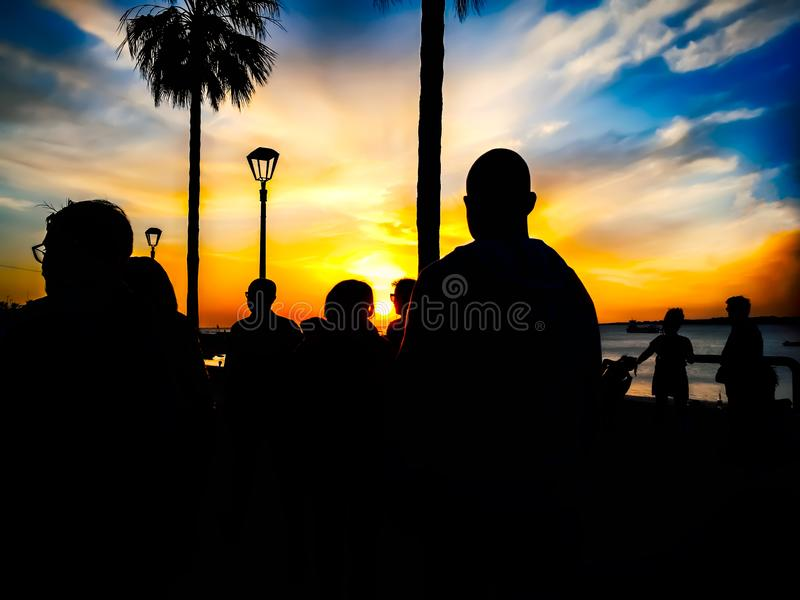 Konturer av folk som går på stranden på solnedgången royaltyfria foton