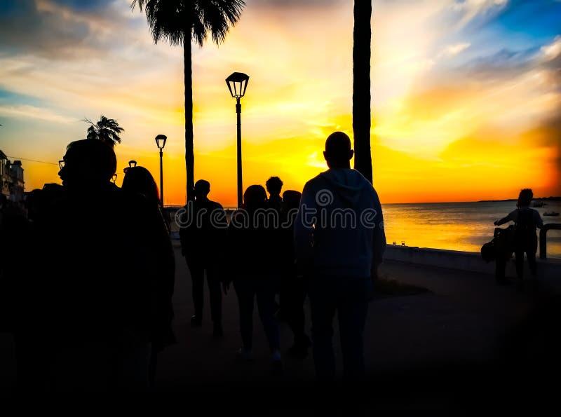 Konturer av folk som går på stranden på solnedgången arkivfoto