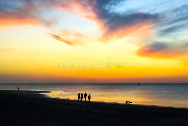 Konturer av folk som går på stranden på solnedgången Episk dramatisk solnedg?ng royaltyfri bild
