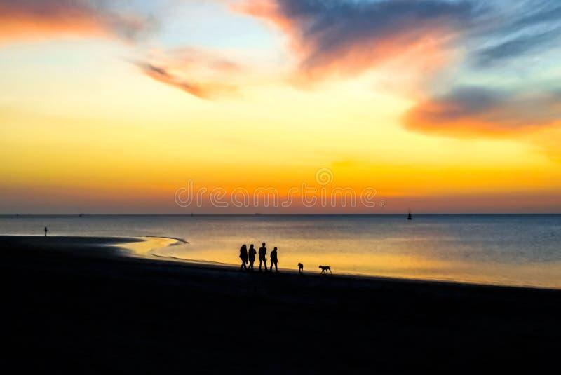 Konturer av folk som går på stranden på solnedgången Episk dramatisk solnedg?ng fotografering för bildbyråer