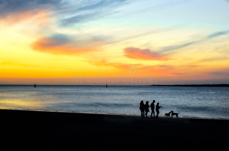 Konturer av folk som går på stranden på solnedgången Episk dramatisk solnedg?ng royaltyfri foto