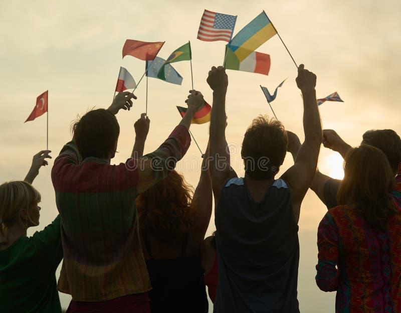 Konturer av folk som rymmer flaggor från olika länder arkivfoton