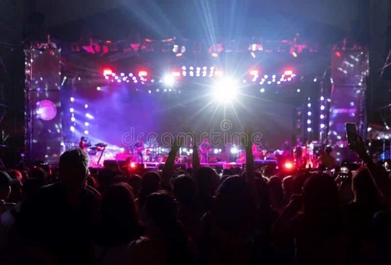 Konturer av folkmassan, grupp m?nniskor som framme hurrar i konsert f?r levande musik av f?rgrika etappljus royaltyfria foton