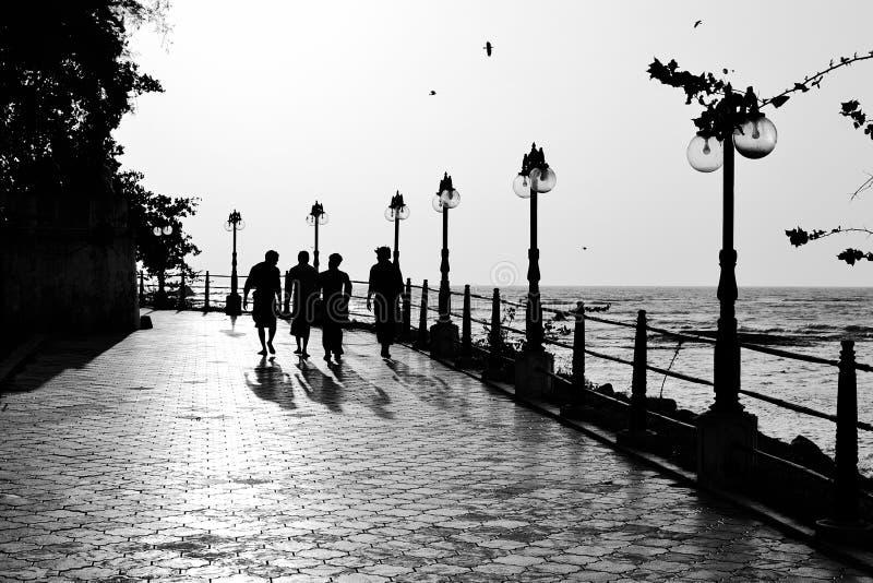 Konturer av fyra män som går på sjösidan, parkerar royaltyfria foton