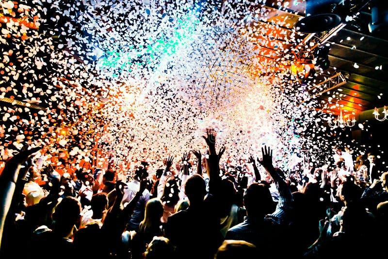 Konturer av konserten tränger ihop framme av ljusa etappljus med konfettier royaltyfri bild