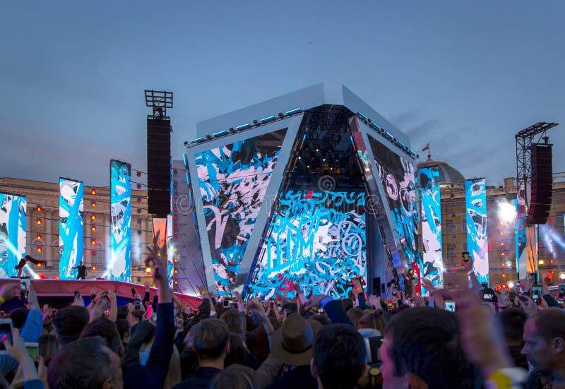 Konturer av konserten tränger ihop framme av ljusa etappljus arkivbild