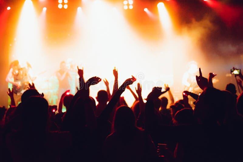Konturer av konserten tränger ihop framme av ljusa etappljus hurra folkmassan av folk med händer upp på populärt vagga musikkonse royaltyfri foto