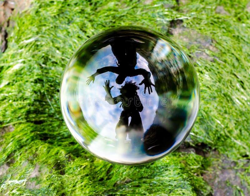 Konturer av mannen och kvinnan reflekteras distortedly i linsen för exponeringsglasbollen som ligger på det gröna gräset royaltyfri bild