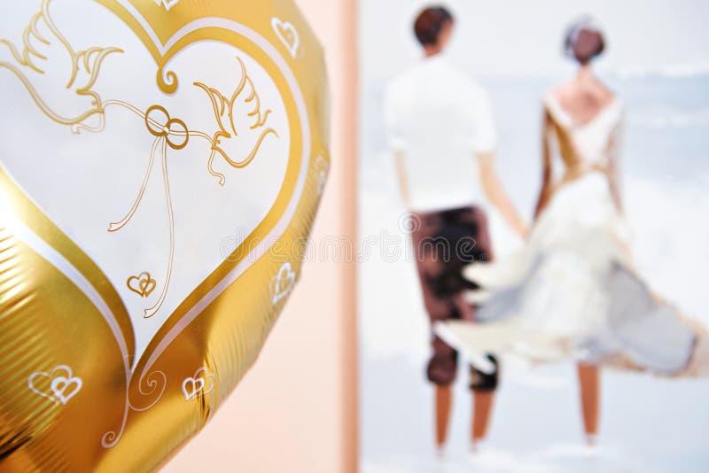 Konturer av nygifta personer på bröllopsresa och den guld- festliga ballongen royaltyfri fotografi