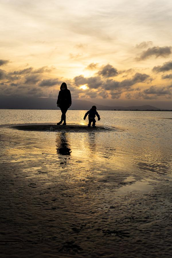 Konturer av oigenkännligt folk på stranden på solnedgången royaltyfri bild
