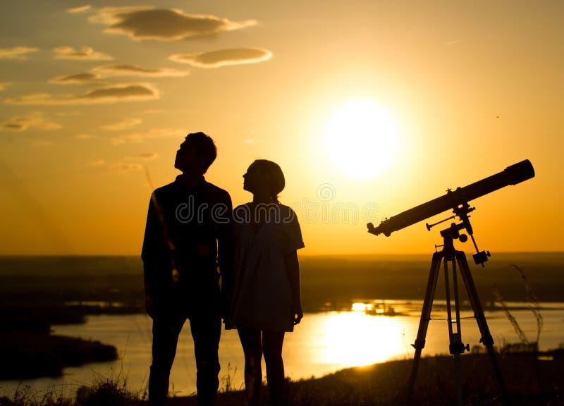 Konturer av par - pojken och flickan nära skjuter ihop på kullen på sommarsolnedgången arkivbilder