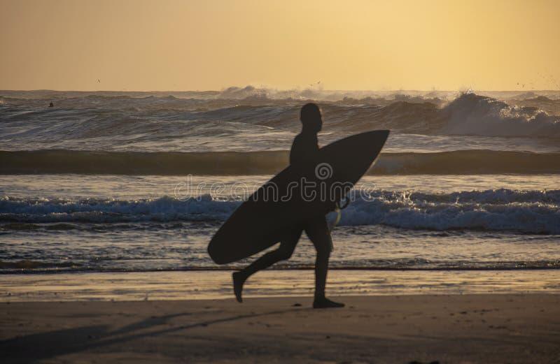 Konturer av surfaren på solnedgången på stranden arkivfoton