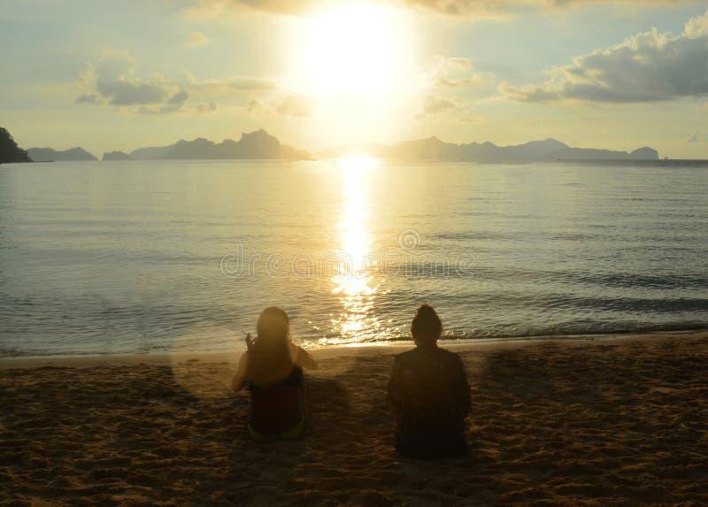 Konturer av två kvinnliga vänner som sitter på stranden under soluppgång i El Nido, Palawan arkivbilder