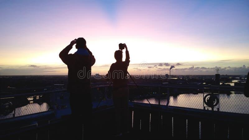 Konturer av två personer på solnedgången Folket tar fotografier av en härlig solnedgång från en högväxt byggnad royaltyfri foto