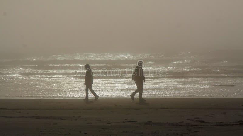 Konturer av två personer som går i motsatta riktningar på en Tillamook strand, Oregon fotografering för bildbyråer
